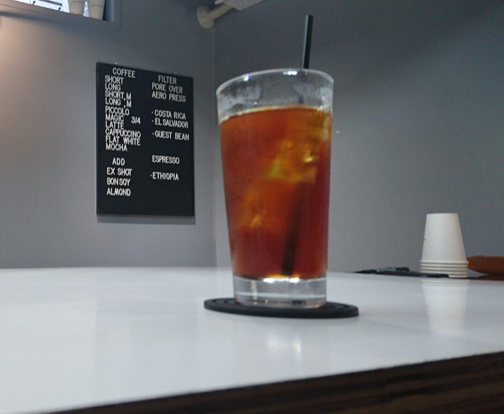 アイスコーヒーとその奥にあるメニュー表