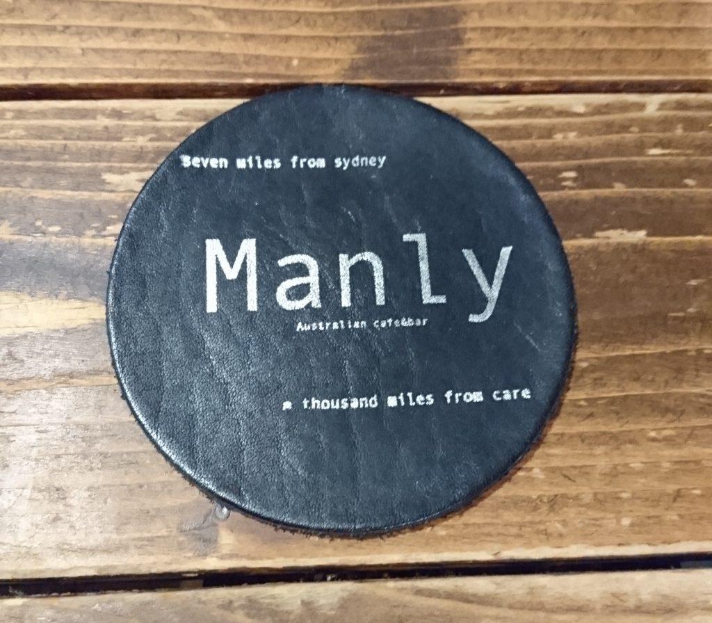テーブルにあるコースター Manlyと書かれている