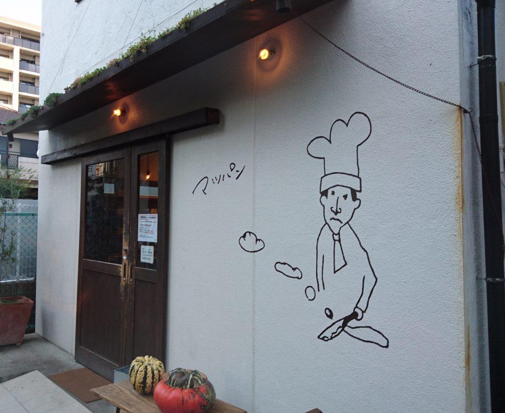 壁に描かれたコックさんの絵と入口
