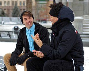 男性2人が外で座って話している