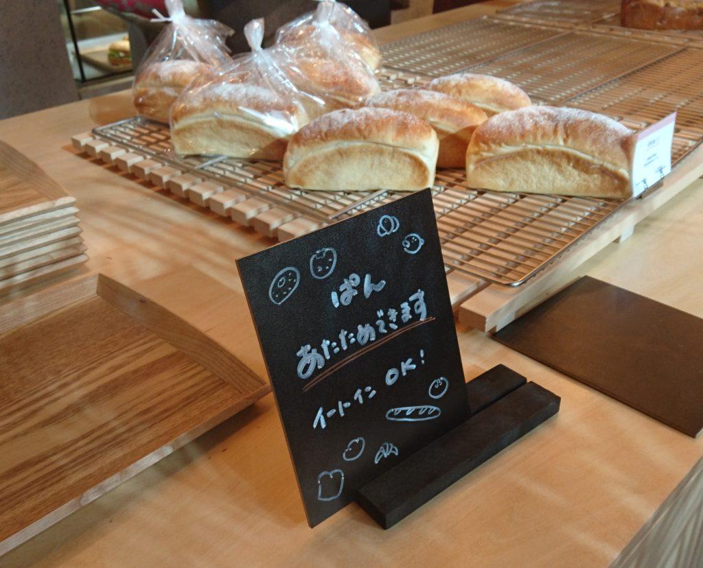 「ぱん あたたためできます」の案内板 パンが並ぶテーブルに置かれている。