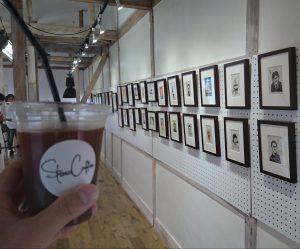 展示絵と手に持ったコーヒー
