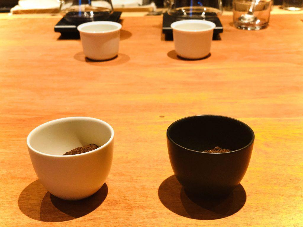 挽いた豆2種類とその奥に写るコーヒー器具ら