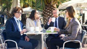 コーヒー飲みながら会議する4人の男女