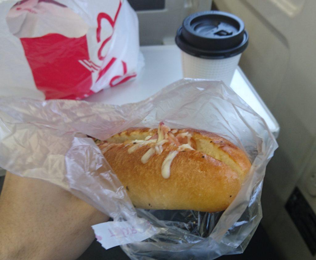 車内テーブルに置かれたコーヒーと左手で持ったベーコンポテトドッグ