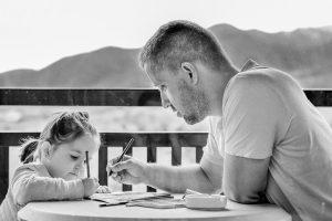 お父さんが子供に教えてる様子 白黒の画像