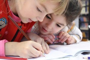 子供2人がノートに向かって字を書いている様子