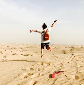 砂漠の上で飛び跳ねる女性