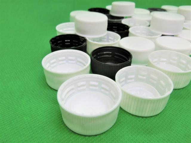 白と黒のペットボトルの蓋がたくさん