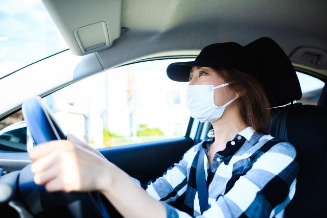 運転するのマスク着用の女性