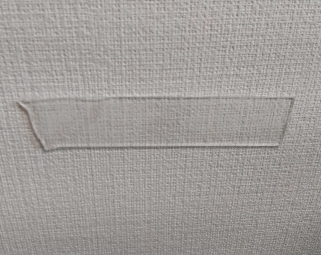 壁にテープを貼る
