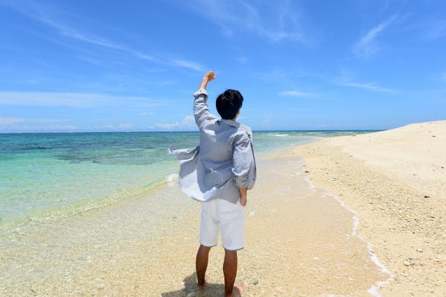 沖縄の海でこぶしを突き上げる男性