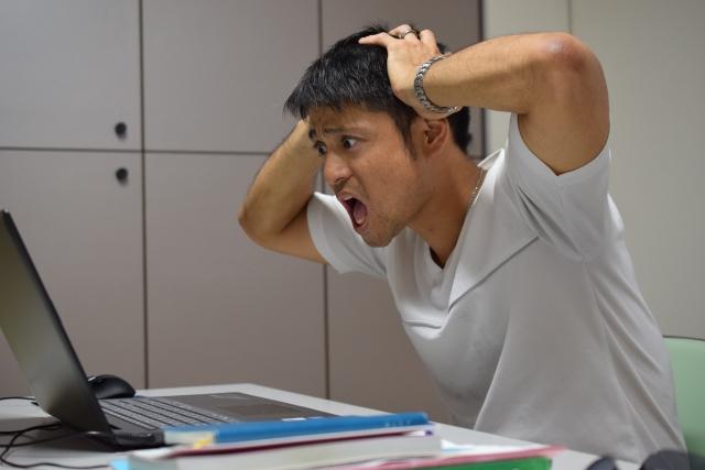 パソコンの前で口を開けて頭を抱える男性