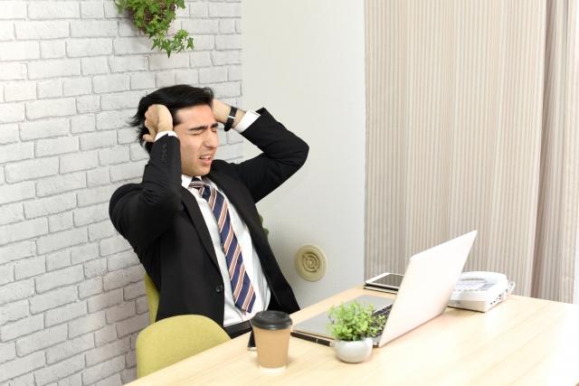 パソコンの前で頭を抱えるスーツを着た男性