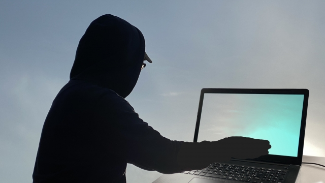 パソコンを操作する怪しい人・詐欺師