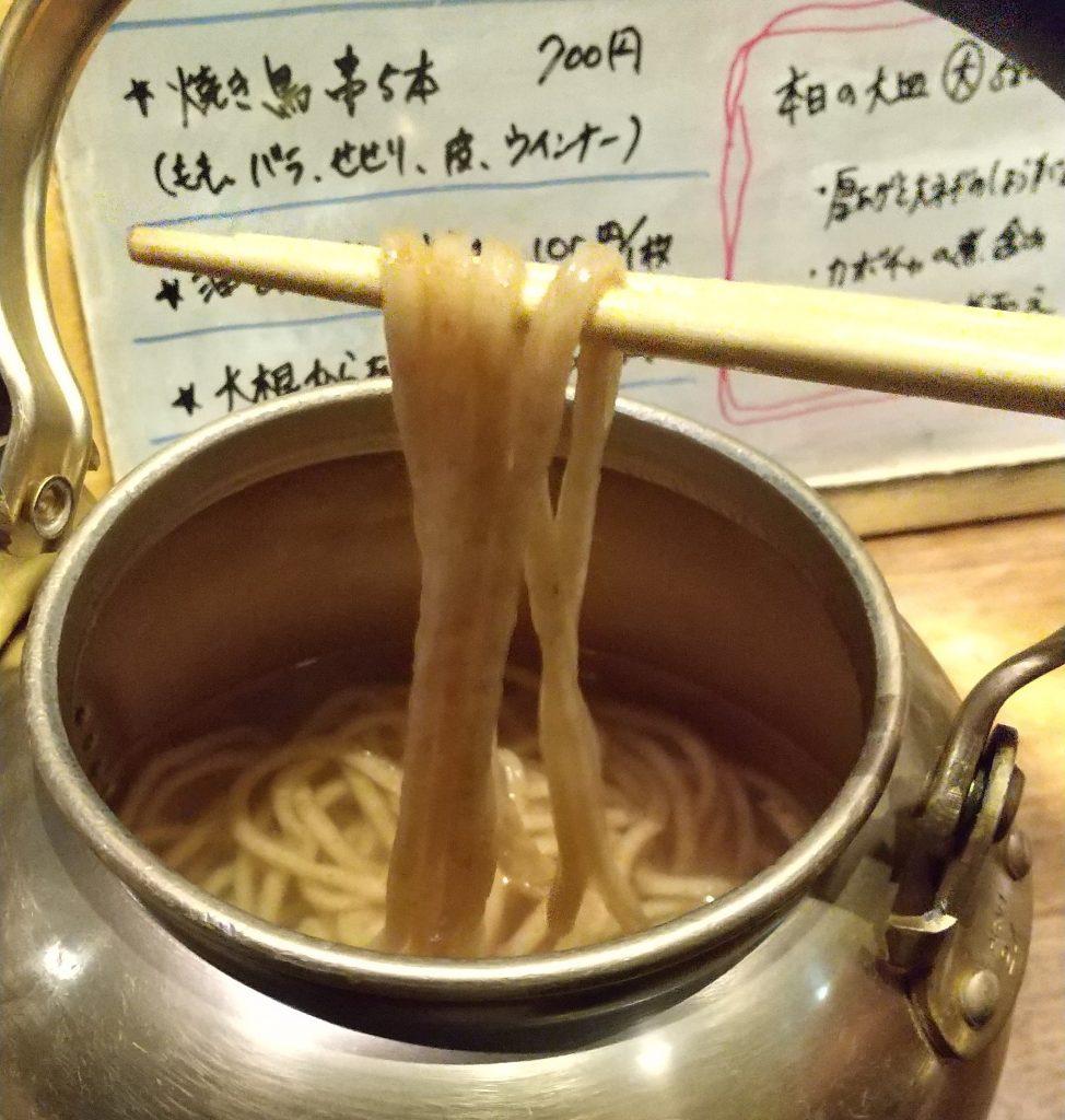 やかんからすくっている麺