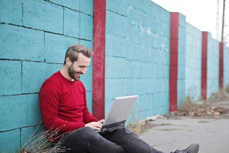 路上でパソコンを使う笑顔の男性