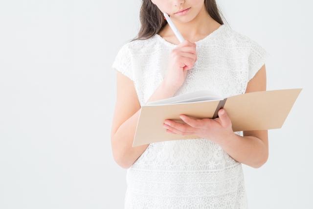 ノートを持って考える女性