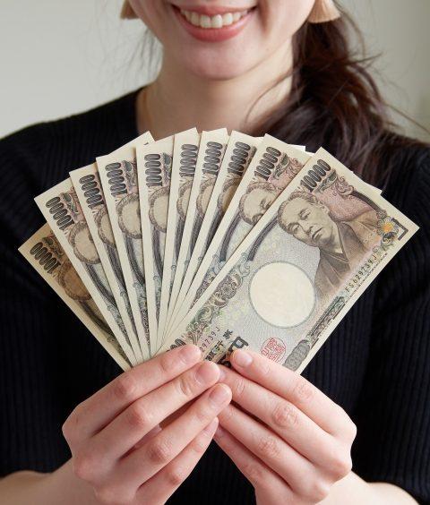 数万円を持って笑う女性