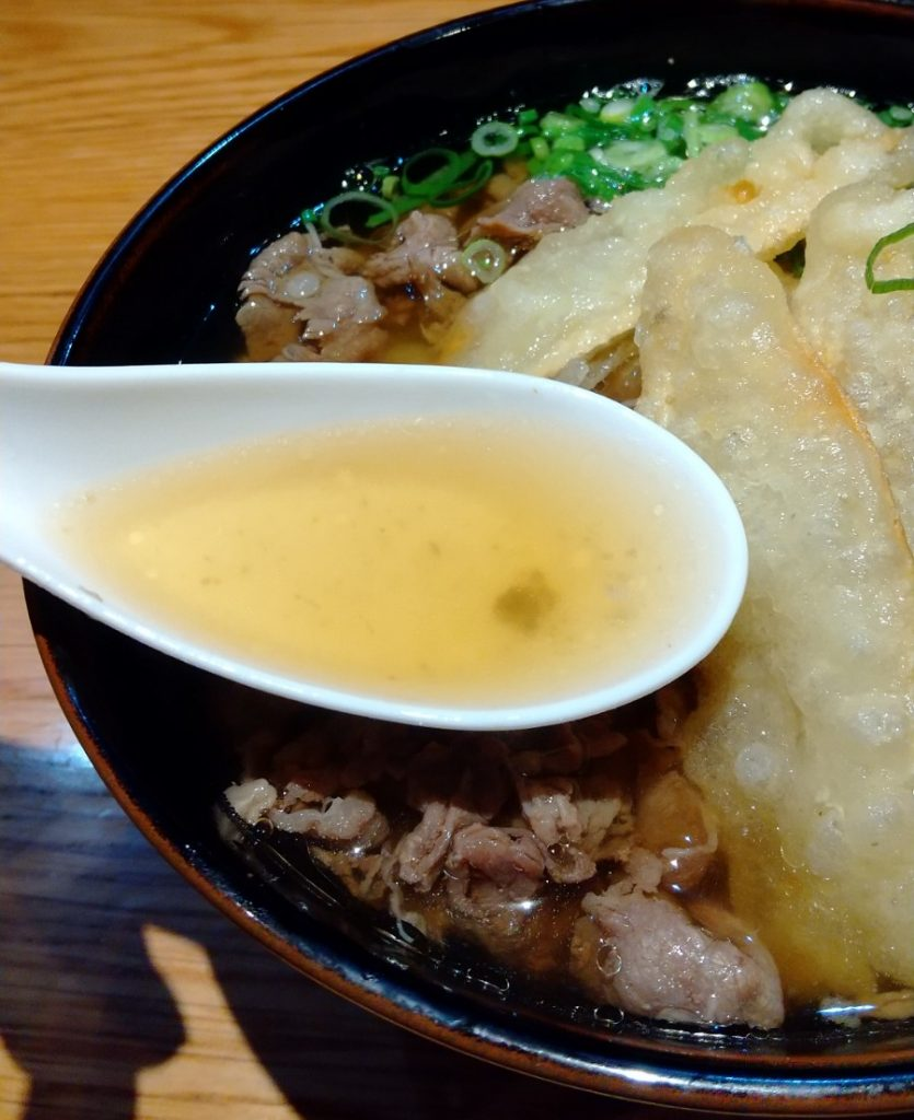 肉ごぼううどん スープを蓮華ですくう