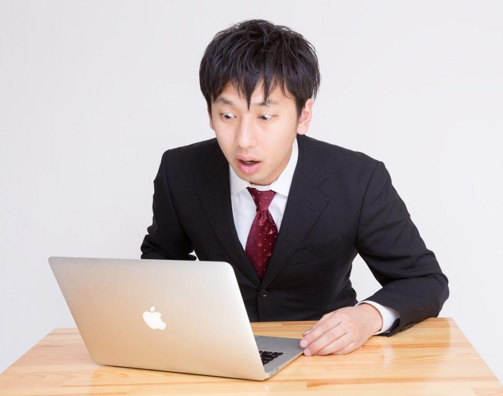 パソコンを見て驚くスーツ男性