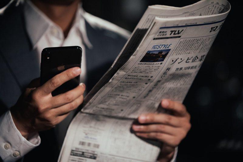 新聞を片手にスマホ操作をする