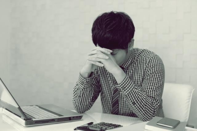 パソコンの前でへこむ男性 白黒画像
