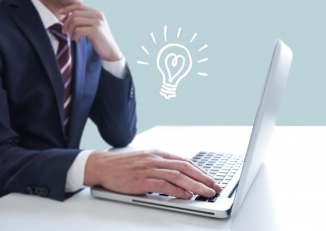 PCを操作するビジネスマンと電球のイラスト